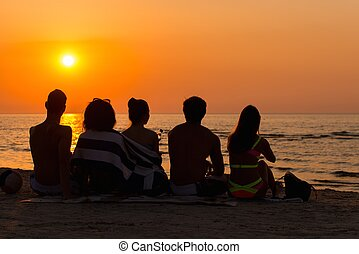 Silhouettes a young people sitting on a beach looking at...