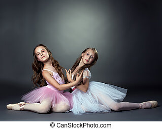 Studio shot of two graceful ballet dancers, on gray...