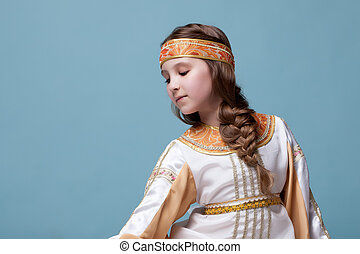 Portrait of charming little folk dancer posing on blue...