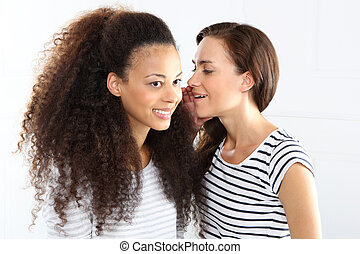 Two cheerful friend. - Two young women whisper in his ear.