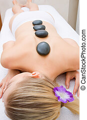 Young woman receiving hot stone treatment