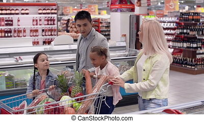 Out Shopping - Tracking shot of family of four walking along...