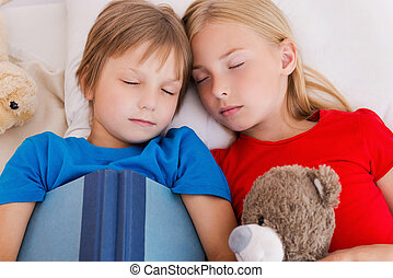 Tired after active day. Top view of two cute children sleeping while lying in bed together