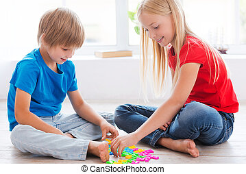 Kids playing at home. Two cute little children playing with plastic colorful letters while sitting on the hardwood floor
