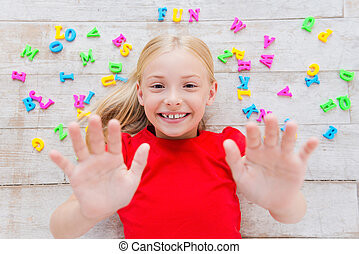 Having fun. Top view of cute little girl stretching out hands and smiling while lying on the floor with plastic colorful letters laying around her