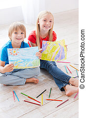 Little artists. Two cute little children showing the pictures they draw while sitting on the hardwood floor