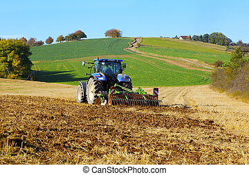 farm tractor on the field working, plowing land