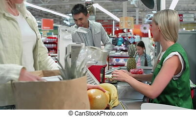 Checkout - Focus shifting from conveyor belt to shopping bag...