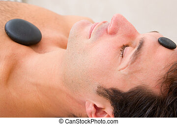 Man receiving a therapy with hot stones