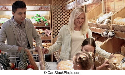 Family of Spendaholics - Family of four selecting bread and...