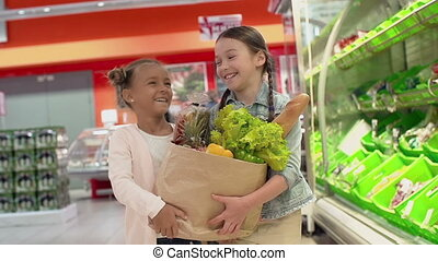 Shopping Spree - Slow motion of two little girls carrying a...
