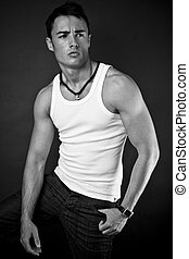 male model - young man in jeans and white vest on black...