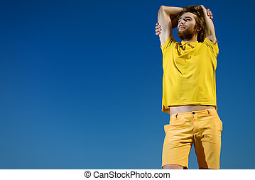 breathe - Handsome young man over blue sky. Summer rest,...