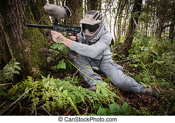 Paintball in the forest - active paintball sport player in...