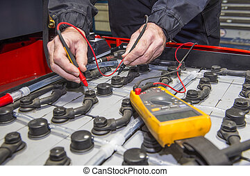 Forklift battery check - Man, checking the nodes of the...