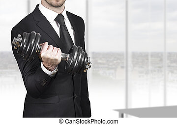 businessman weightlifting in office - businessman in black...