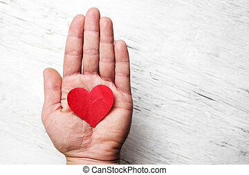 Heart in human hand. White wood background