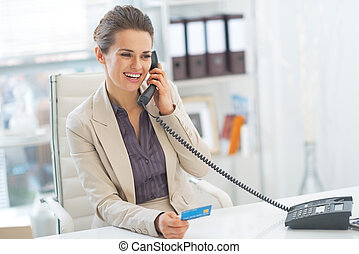Smiling business woman talking phone in office