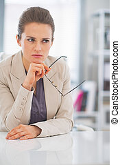 Thoughtful business woman with eyeglasses in office