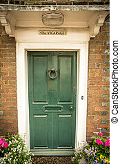 Vicarage - Pretty doorway flanked by flowers to village...