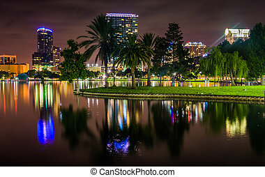 Buildings and palm trees reflecting in Lake Eola at night, Orlan