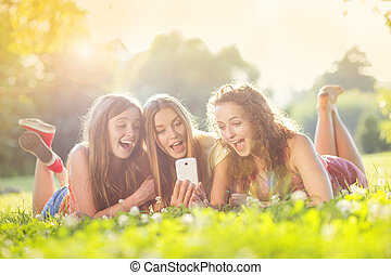 Girls lying on grass - Three beautiful girls laughing...