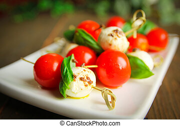 Caprese - Bocconcini with basil and cherry tomatoes on...