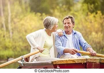 Senior couple on boat - Senior couple paddling on boat with...