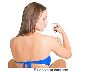 Woman applying sunscreen on her arm, isolated in white