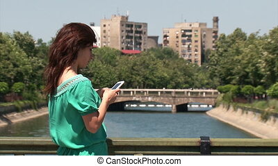 Girl standing on a bridge - texting