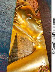 Face of Reclining Buddha gold statue in Wat Pho buddhist...