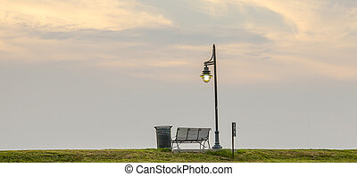 romantic sky at sunset with bench at the mississippi in...