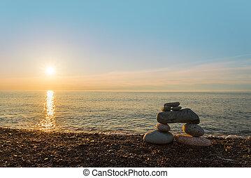 Inukshuk stones on ocean shore