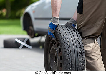 Man rolling a spare wheel - Close-up of a man rolling a...