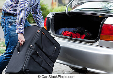 Man putting suitcases in car trunk for a journey - Close-up...