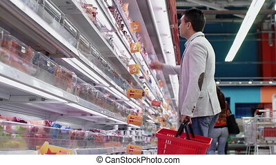 Dietary Product - Low angle of guy shopping in dairy...