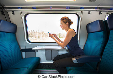 Young woman traveling by train, using her smartphone