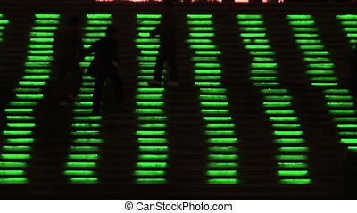 Neon Lit Stairs - People walking up neon lighted steps at...
