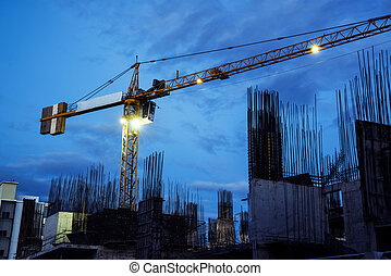 Buildings under construction with cranes at evening