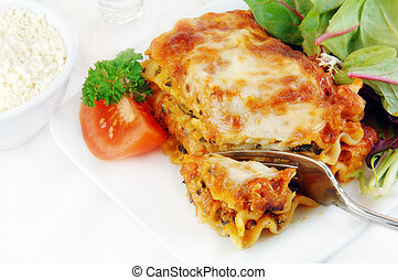 Lasagna With Salad - Spinach lasagna with salad on a white...
