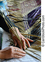 Maori woven artwork - Hands of an old Maori woman weaving a...