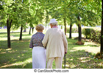 Walking in summer - Back view of serene senior couple taking...