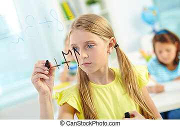 Doing sums - Portrait of lovely girl doing sums on...