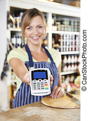 Sales Assistant In Food Store Handing Credit Card Machine To Cus