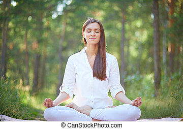Spiritual practice - Portrait of calm woman sitting in pose...