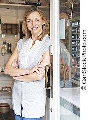 Owner Of Gift Shop Standing In Doorway