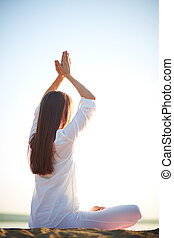 Unity of body and mind - Side view of young woman doing yoga...
