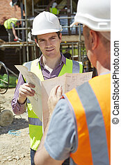Architect Discussing Plans With Builder On Construction Site