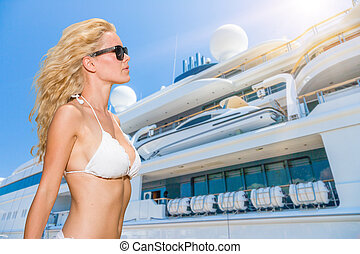 Young woman posing is front of super yacht in Greece