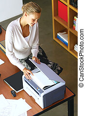 a businesswoman using copier machine - Pretty young...